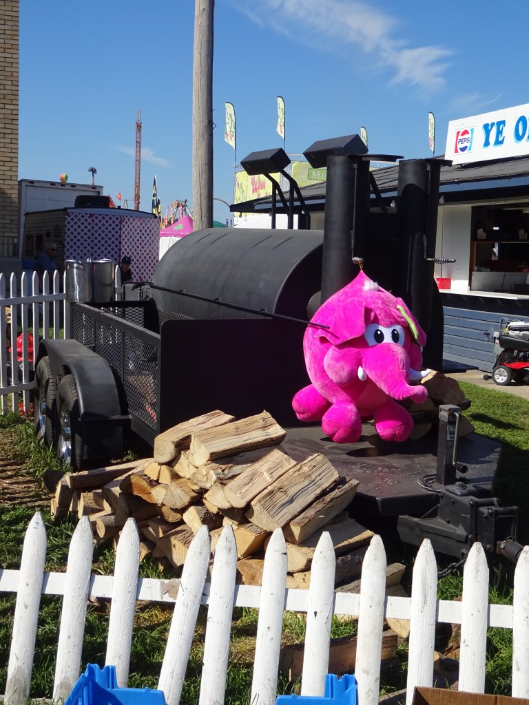 Maybe you had a few beers on the midway, but you really did see this pink elephant guarding the Grange stand's smoker.